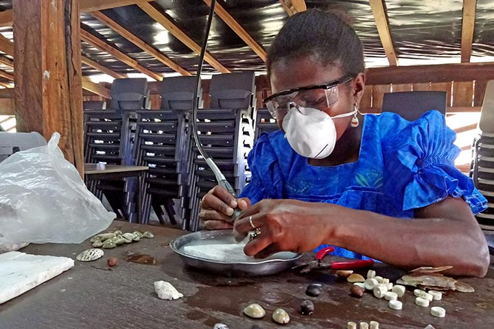 A woman preparing shells for jewellery