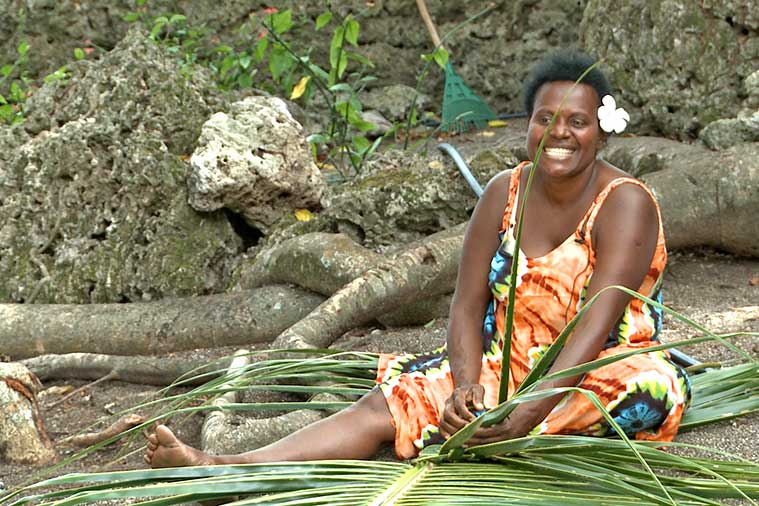 A woman weaving a palm leaf