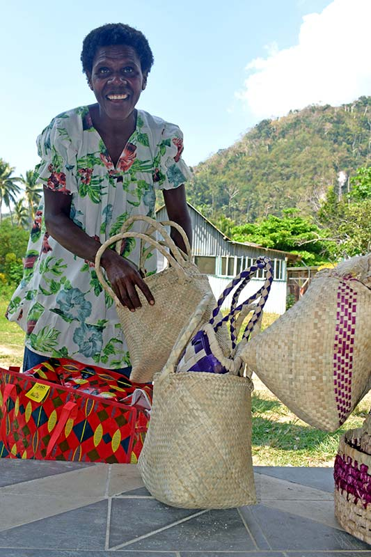 A woman packing her bag weaving products
