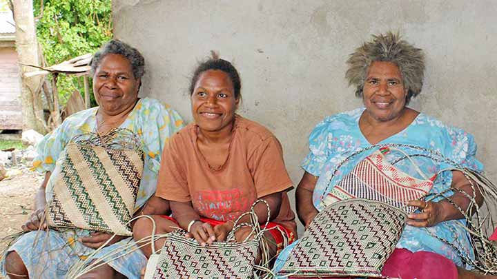 Women proudly displaying their woven bags